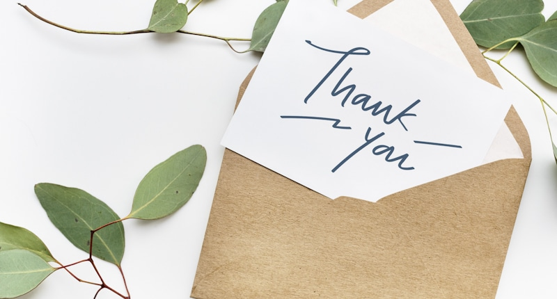 thank you note on envelope with leaves around